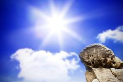 Large rock overlooking bright sky Royalty Free Stock Image