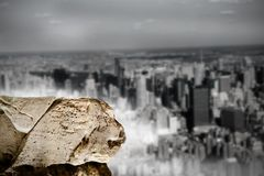 Large rock overlooking huge city Royalty Free Stock Images