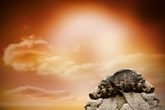 Large rock overlooking orange sky Stock Photo