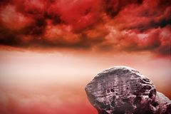 Large rock overlooking red sky Stock Images
