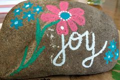Joy - Painted Rock with Pink and Blue Flowers royalty free stock image