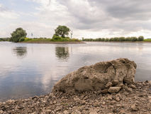Large rock by quiet river in Doesburg, Holland Royalty Free Stock Photos