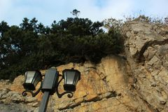 Green trees, nature of the Crimea,a large rock and a street lamp, a quay and a stone coast, rocks on the seashore, a tall black p. A large rock and a street lamp stock images