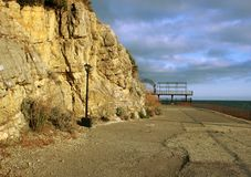 Green trees, nature of the Crimea,a large rock and a street lamp, a quay and a stone coast, rocks on the seashore, a tall black p. A large rock and a street lamp stock photos