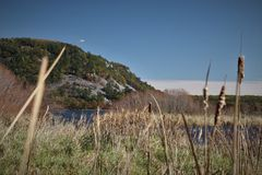 Rocky Bluff with Cattails. Large rocks along the bank of a deep blue lake. Fall color with the last stages of cattails in the foreground royalty free stock image