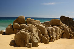 Large Rocks on Beach. Boulders along a sandy beach with a green and blue sea behind them Royalty Free Stock Photos