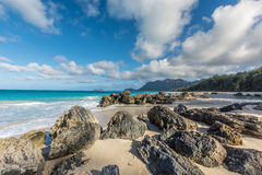 Large rocks on a Hawaiian beach. Large rocks and beautiful emerald green waters of Waimanalo on a sunny day on the island of Oahu, Hawaii, with the forest and Stock Images