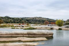 Free Large Rocks In The Water In The Pedernales River In The Autumn In Texas With Tourists Sitting On Rocks In Distance And Insulators Stock Image - 143832181