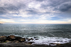 Large rocks, many clouds, and the horizon on a seascape Royalty Free Stock Photography