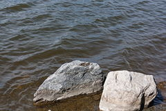 Large rocks near the shore lapped by the waves of the lake Royalty Free Stock Photos