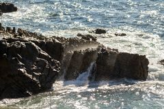 Large rocks in the ocean. Large rocks and cliffs in the ocean with waves crashing on them. no people, ocean scene stock photo