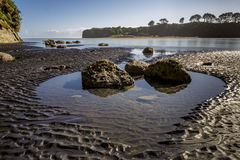 Large rocks in pool of water on black sandy beach leading to Three Sisters and The Elephant, New Zealand Royalty Free Stock Photos