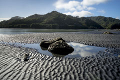 Large rocks in pool of water with cloud reflection at North Taranaki, New Plymouth Royalty Free Stock Photos