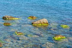 Large rocks in the sea. Covered with algae stock photography