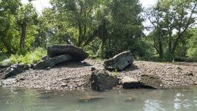Illinois River in eastern Oklahoma, rocky shoreline and lush vegetation. Large rocks and smaller pebbles line the shore of the Illinois River near Gore, Oklahoma royalty free stock photo