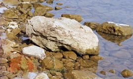 Large rocks and stones in shallow waters along lake shoreline stock photo