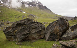 Large rocks. Two large rocks on grass with mountains in the background Stock Images