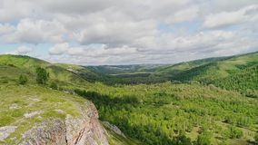 Large rocky cliff and mountain valley. Aerial view of a beautiful hilly landscape. Panorama of mountains stock video