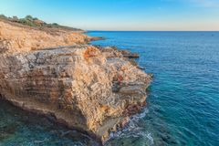 Large rocky coastline under blue sky. In the ocean Stock Photos