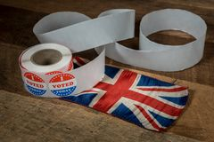 Roll of I Voted Today paper stickers on table with UK Flag stock images