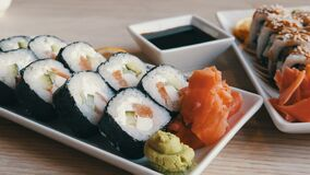 Large roll sushi from Japanese cuisine lie on a table in a stylish restaurant, next to a sauce bowl for soy sauce. Wasabi, ginger and a slice of lemon stock video