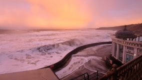 Rolling storm Waves hitting the shore. Large rolling wave about to breach ashore in Scarborough with an eeire pink and orange sky Royalty Free Stock Images