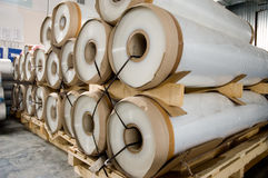 Large rolls of transparent polyethylene lie on a pallet. Royalty Free Stock Image