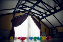 Large room with a large window and curtains with inflatable colored balls. During the holiday Stock Image