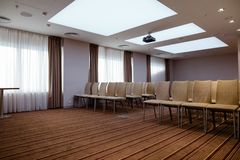 Large room with many cosy beige chairs provided for events. Order conference services Stock Images