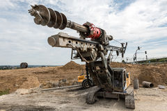 Large rotary drill and excavator on construction site Stock Images