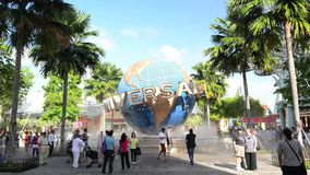 The large rotating globe fountain in front of Universal Studios on January 13, 2015 in Sentosa island, Singapore. SINGAPORE - JANUARY 13 Tourists and theme park stock video footage