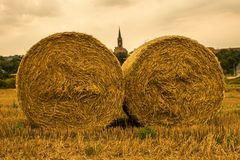 Large round bales of straw and the church in the background. stock images