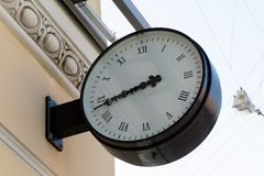 Clock with an arrow on the wall. Large round clock with an arrow on the wall of a building royalty free stock image