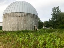 A large round concrete and metal barn for storing grain and corn stock photography