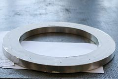 A large round shiny metal ring with small holes, holes, a flange on the working iron table in the factory, the workshop. royalty free stock photos