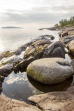 Large round stone lies on the shore of Lake Ladoga. At sunrise on a background of pine trees and islands stock photo