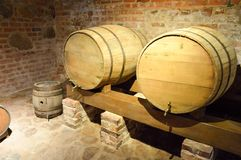 Large round wooden barrels for beer, wine in the old cellar of the Middle Ages made of brick.  royalty free stock photography