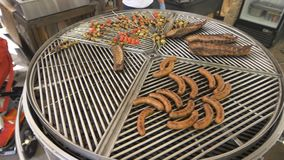 A large rounded grill is divided into segments, wrapped around its axis, on a grill variety and meat and vegetables on. Kebabs, the chef puts the sausages on stock footage