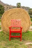 Large rounded hay stack on green grass with red chair Royalty Free Stock Photos