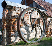 Large rusted metal industrial wheel against the background of an Royalty Free Stock Photos