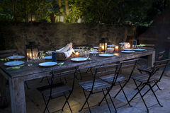 Large rustic table prepared for a outside dinner at night. Large rustic table on the terrace prepared for a outside dinner with friends from the evening until Royalty Free Stock Images
