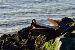 Large rusty anchor on  group of rocks Royalty Free Stock Image