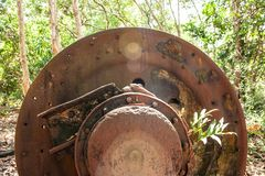 Large rusty gear of Tin Dredge in the deserted tin mine. Tropical plant growing in the rusty gear, dry leaves fall on the ground,. Forest backgrounds. Thai stock photos