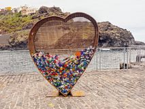 A large rusty, transparent metal heart as a recycling container of plastic closures. For reprocessing. In Garachico on Tenerife stock photography