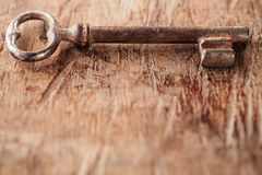 Large rusty vintage metal key on old wooden background Stock Images