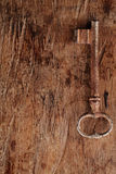 Large rusty vintage metal key on old wooden background Royalty Free Stock Photo