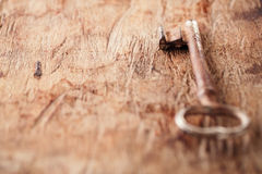 Large rusty vintage metal key on old wooden background Royalty Free Stock Images