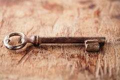 Large rusty vintage metal key on old wooden background Royalty Free Stock Image