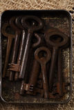 Large rusty vintage metal keys in tin Stock Image