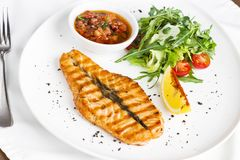 The large salmon steak red fish on the grill with lemon, sauce and vegetables. The large salmon steak red fish on the grill with lemon, sauce with vegetables and royalty free stock photo